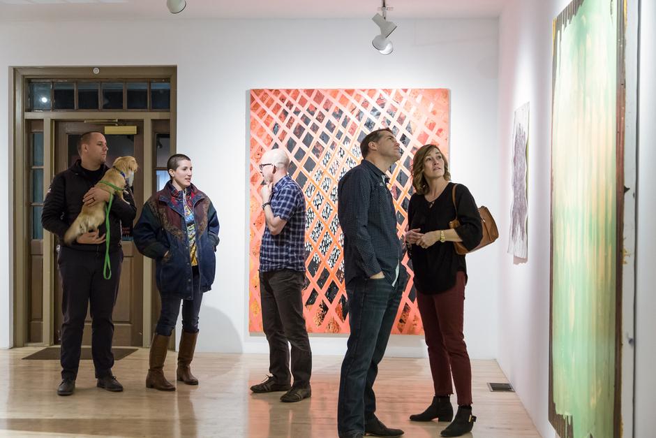 Gallery attendees look at artwork.